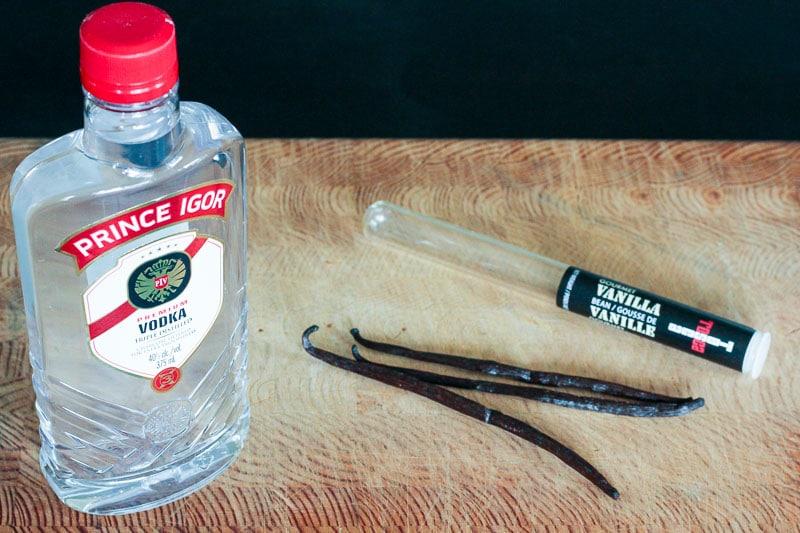 Bottle of Vodka and Vanilla Beans on Wooden Board.