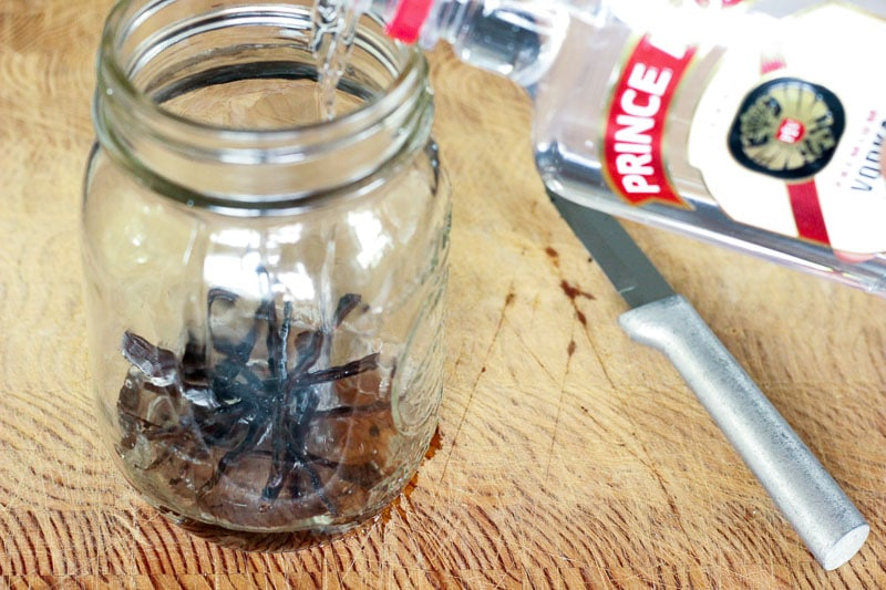 Pouring Vodka into Mason Jar with Vanilla Beans in It.