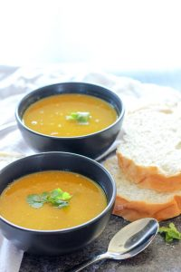 Coconut Curry Carrot Soup topped with Cilantro in Black Bowls.
