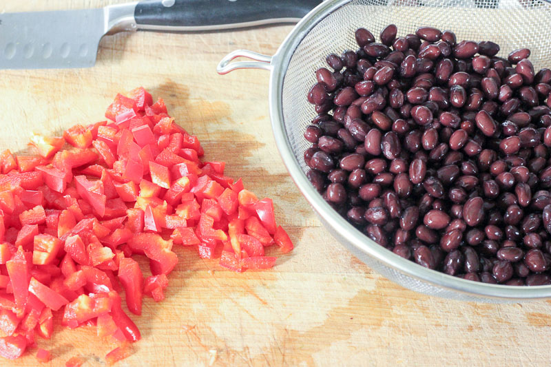 Chopped Red Peppers on Wooden Board and Black Beans in Metal Colander.
