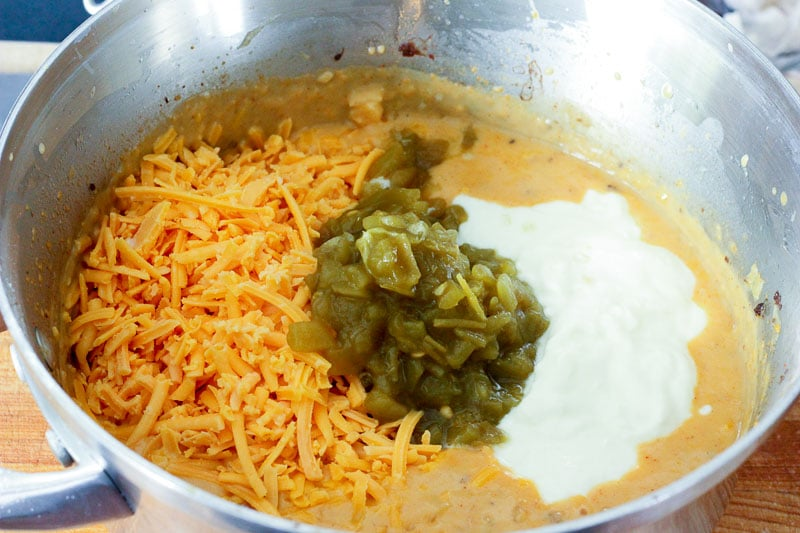 Adding Shredded Cheddar Cheese, Chopped Green Chillies and Yogurt to Metal Pot.