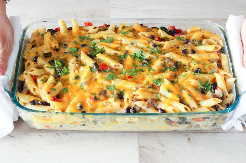 Chile Con Queso Pasta Bake topped with Parsley in Glass Baking Dish.