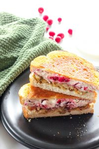 Grilled Turkey, Cranberry and Cream Cheese Sandwich on Black Plate.