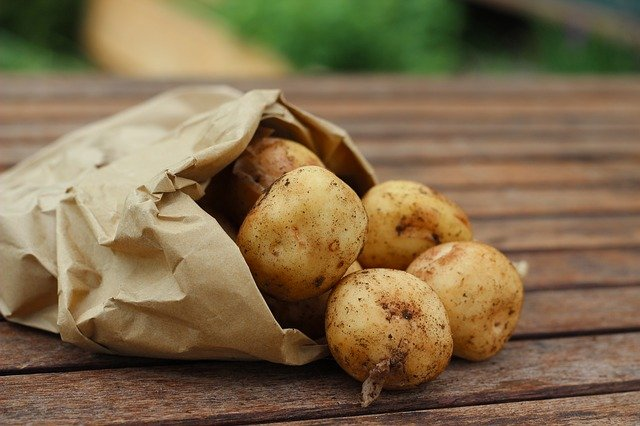 Potatoes in a paper bag. Potatoes are cheap, filling, versatile and delicious. Eat more of them to save money on groceries!
