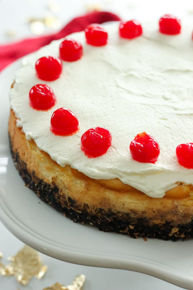 Chocolate Cherry Coconut Cheesecake topped with Whipping Cream and Cherries.
