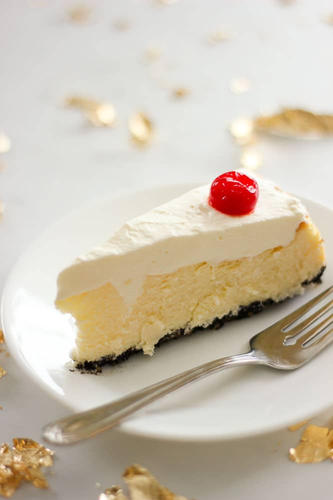 Slice of Chocolate Cherry Coconut Cheesecake topped with Whipping Cream and a Cherry.