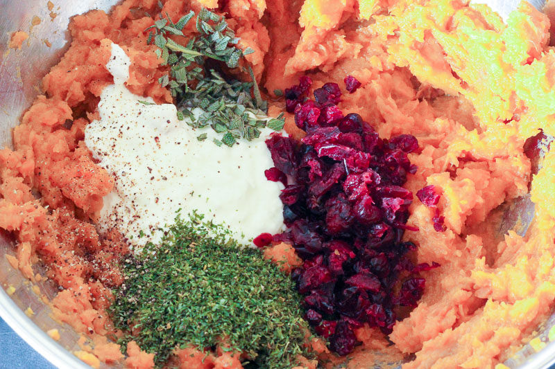 Adding Herbs, Yogurt and Cranberries to Whipped sweet potatoes.