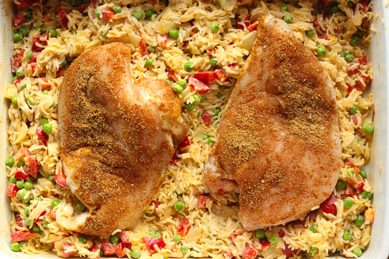 Nestle chicken on top of cooked rice for One Pan THAI Chicken and Rice Bake