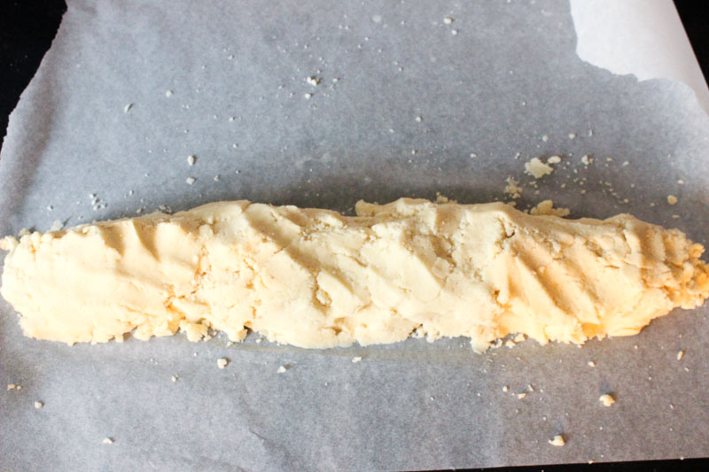 Eggnog Cookie Dough Formed into a Log on Parchment Paper.
