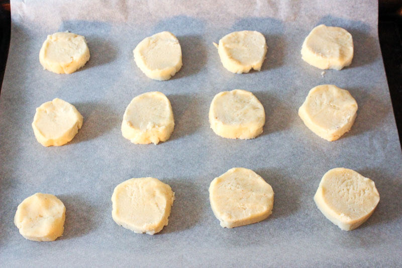 Sliced Eggnog Cookie Dough Circles on Parchment Paper.