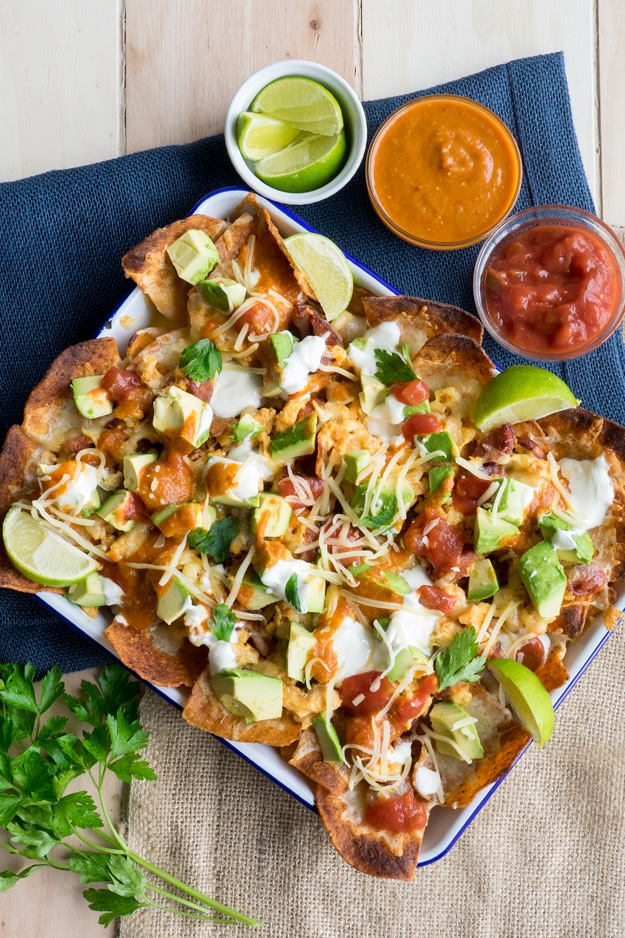 Nacho Chips Topped with Chorizo, Egg, Avocado and Lime Wedges.