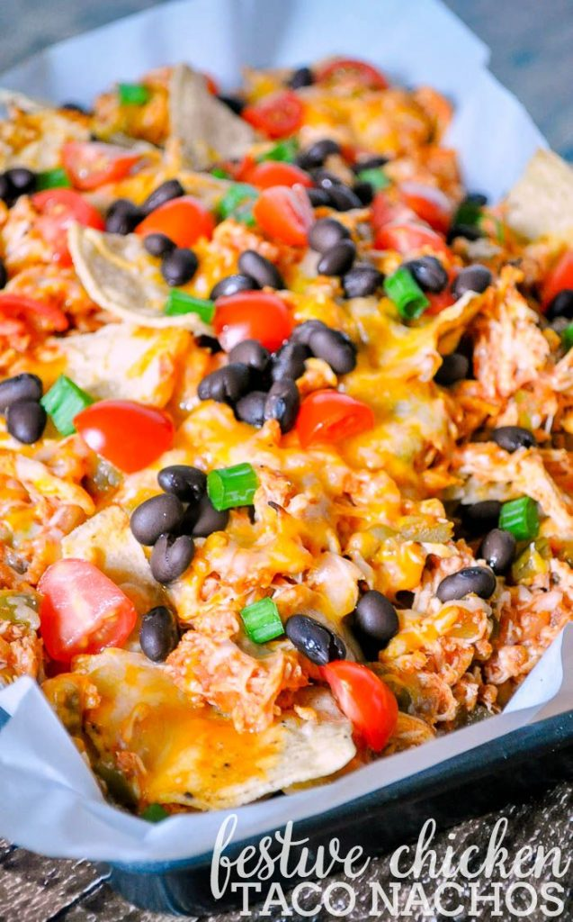 Chicken Taco Nachos Topped with Black Beans, Green Onions and Tomatoes.