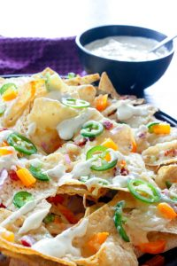 Nacho Chips topped with Cheese, Jalapeños, Orange Peppers and Garlic Cream Sauce.