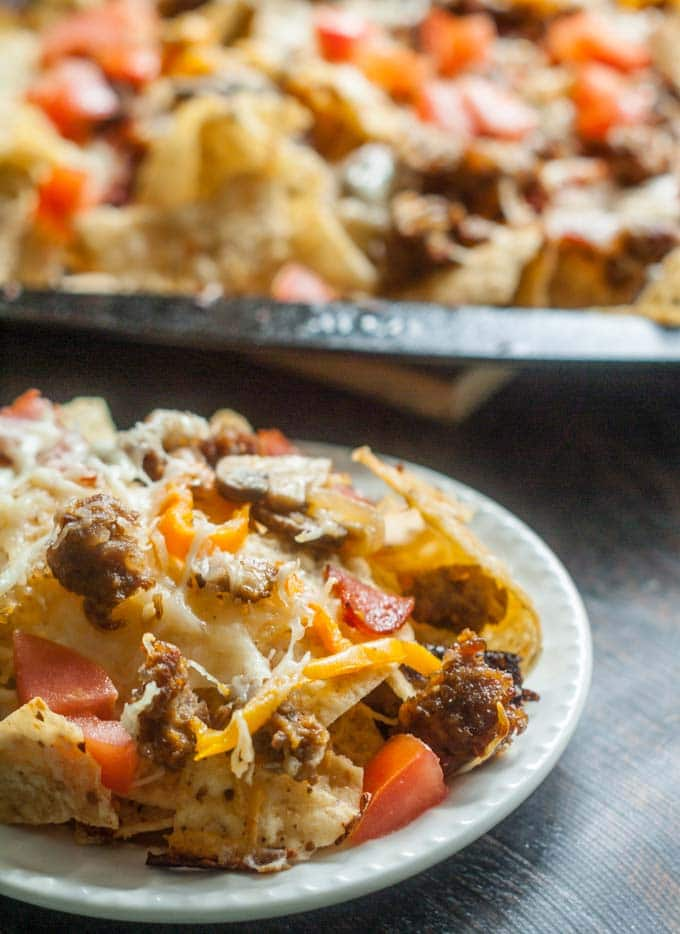 Nacho Chips topped with Sausage, Tomatoes and Cheese on White Plate.