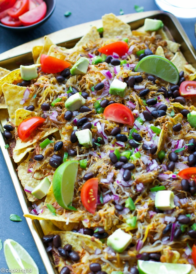Nacho Chips in Sheet Pan topped with Tomatoes, Avocado, Black Beans and Lime Wedges.