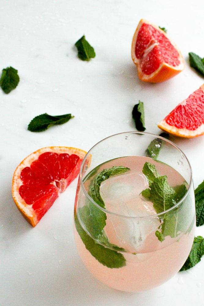 Grapefruit Mint Infused Water in Glass with Ice Cubes and Mint Leaves.
