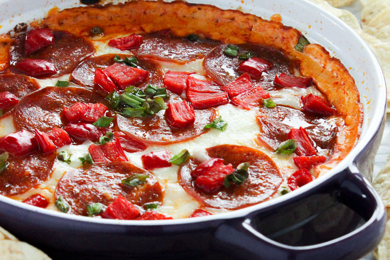 Pepperoni Pizza Dip topped with Red Peppers and Green Onions in Purple Baking Dish.