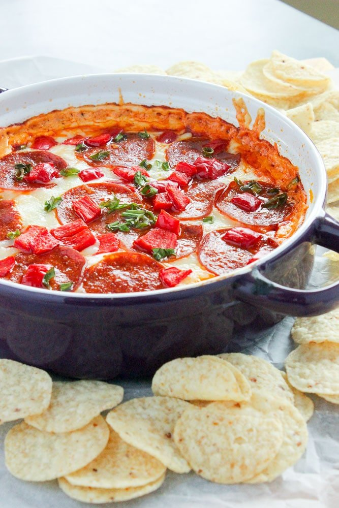 Pepperoni Pizza Dip Topped with Red Peppers and Parsley in Purple Baking Dish.