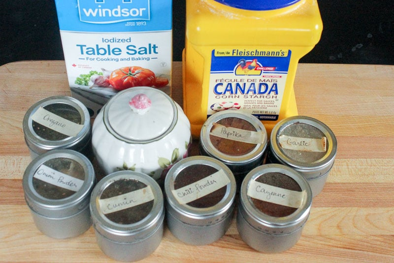 Table salt, cornstarch, oregano, onion powder, cumin, chili powder, paprika, cayenne pepper, garlic powder and sugar in containers on a wooden cutting board.