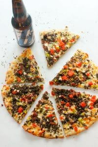 Sliced Bacon Cheeseburger Pizza and a Bottle of Beer on White Board.