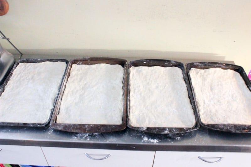 Pizza Dough Spread in Four Rectangular Sheet Pans.
