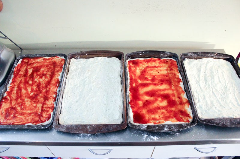 Spreading Pizza Sauce on Pizza Dough in Rectangular Sheet Pans.