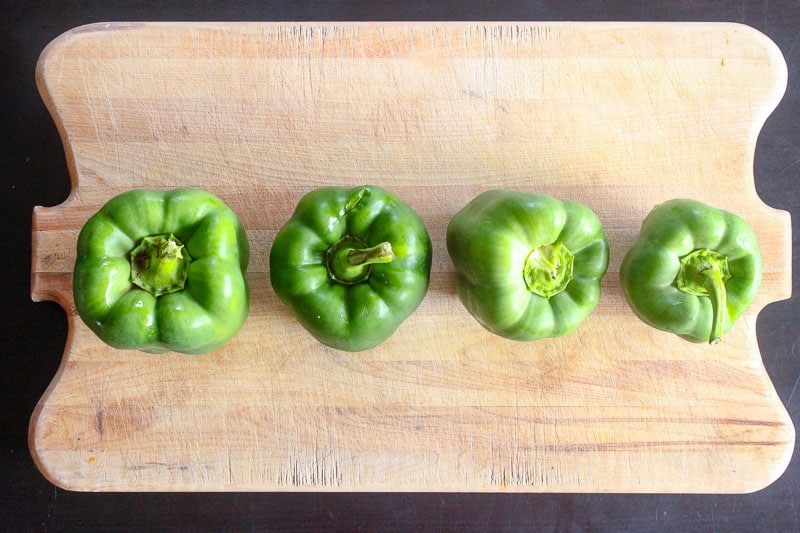 Four green bell peppers lined up on a Wooden cutting board.