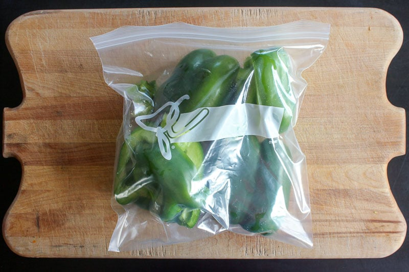 Halved Green Peppers in Resealable Plastic Bag on Wooden Board.