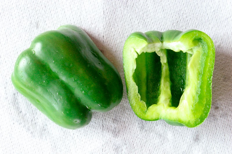 Green pepper sliced in half with water drops on it, draining on a paper towel