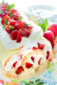 Strawberry Cake Roll topped with Whipping Cream and Sliced Strawberries.
