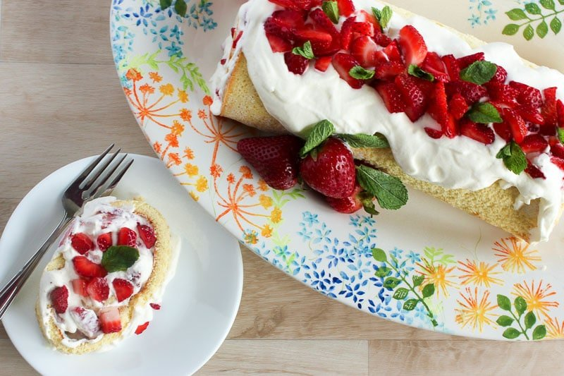 Strawberry Cake Roll on a colourful platter, with a slice cut off and placed on a plate with a fork.