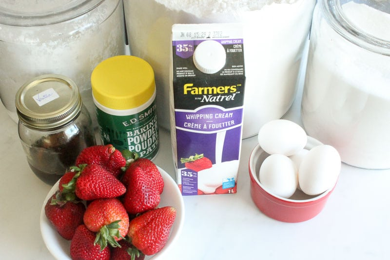 Jar of icing sugar, jar of flour, jar of sugar, jar of homemade vanilla extract, tub of baking powder, carton of whipping cream, dish of eggs and bowl of fresh strawberries
