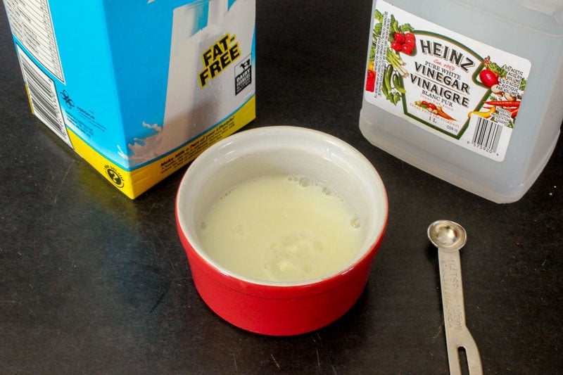 Carton of skim milk, bottle of vinegar and small dish with milk and vinegar mixed together in it