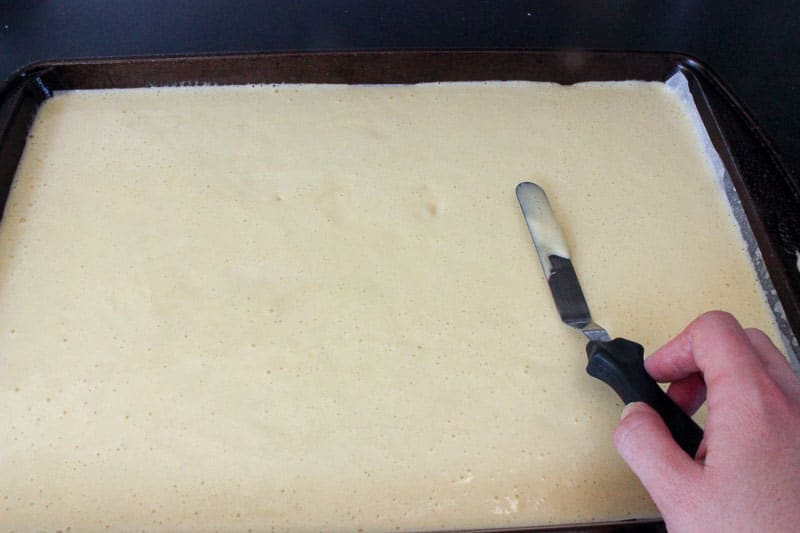 Offset spatula levelling cake batter in a cookie sheet