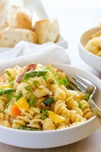Bowl of creamy fusilli pasta with bell peppers, green beans and fresh herbs.