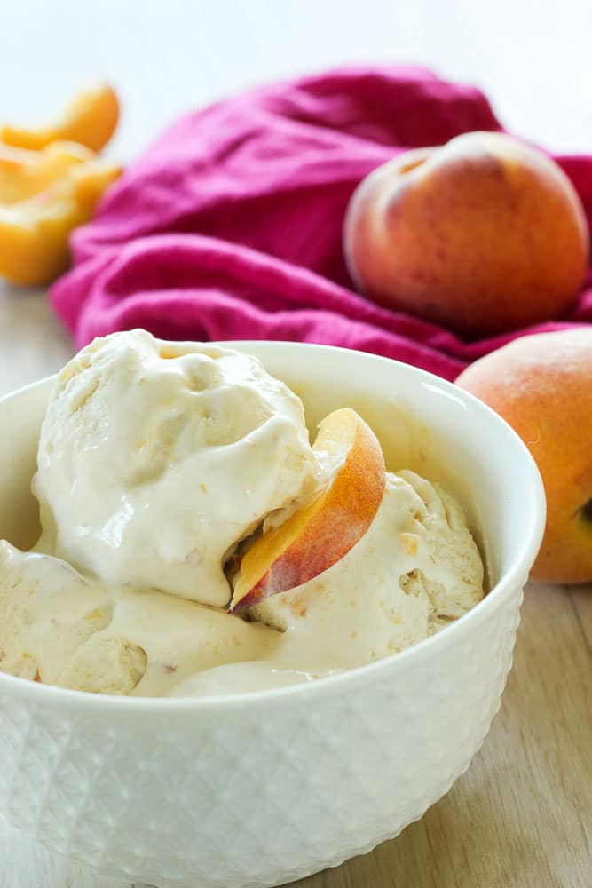 Peach ice cream topped with Peach Slice in a white bowl.