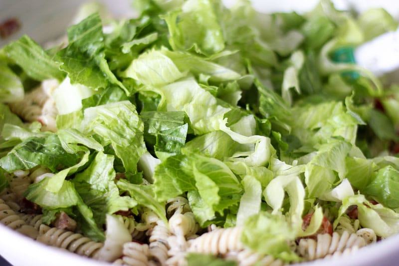 Mixing lettuce into BLT pasta salad.