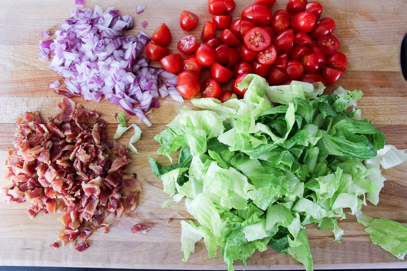 Diced red onion, halved cherry tomatoes, crumbled bacon and chopped romaine lettuce on wooden board.