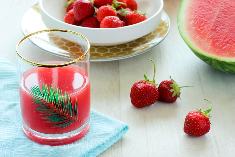 Red juice, with strawberries and watermelon in the background