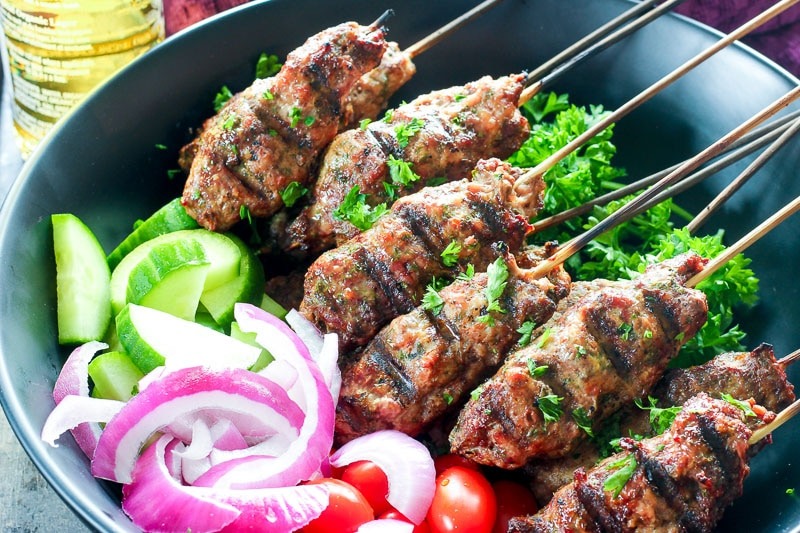 Platter of beef kebabs, cucumber, red onions and grape tomatoes.