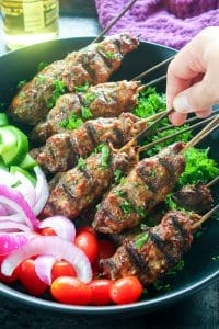 Beef Kebab Skewers Topped with Parsley and Vegetables in Black Bowl.