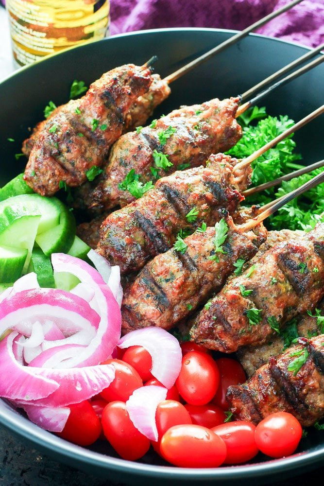 Beef kebabs on skewers, with grape tomatoes, red onion and cucumbers in Serving Dish.