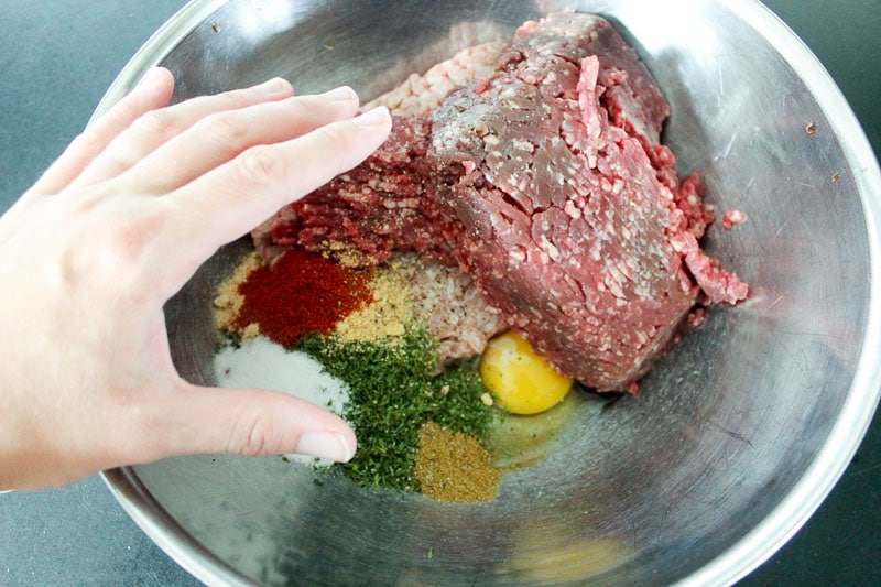 Hand mixing ingredients for beef kebabs - ground meat, eggs and spices