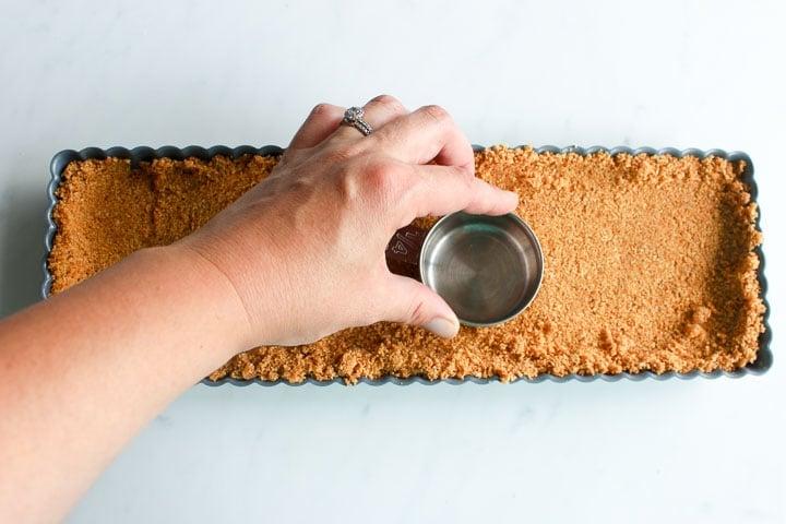 Pressing graham crust into tart pan