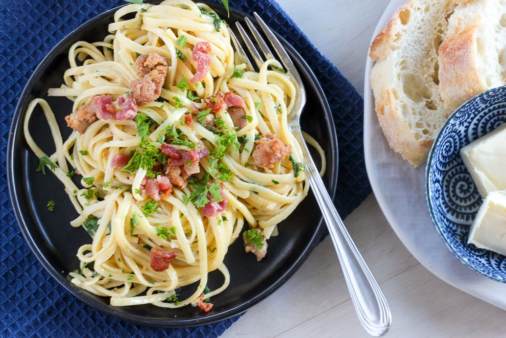 Plate of creamy sausage pasta topped with parsley with bread and butter on the side