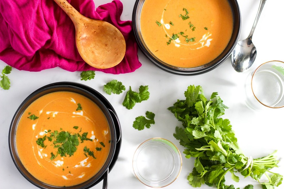 Bowls of bright orange Thai butternut squash soup ready to eat
