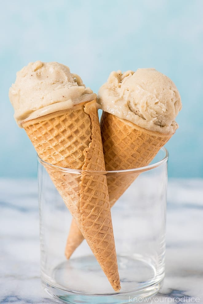 Two ice cream cones filled with banana ice cream, standing in a glass