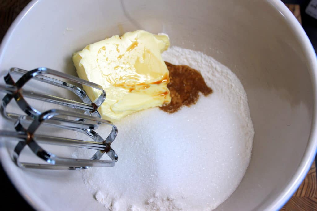Butter, vanilla extract, white sugar and flour in mixing bowl with metal beaters.