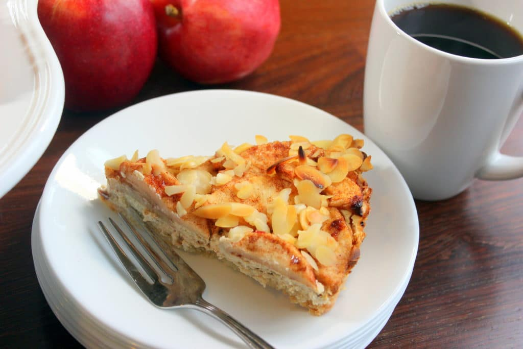 Apple pie and fork on white plate with black coffee and apples in background.