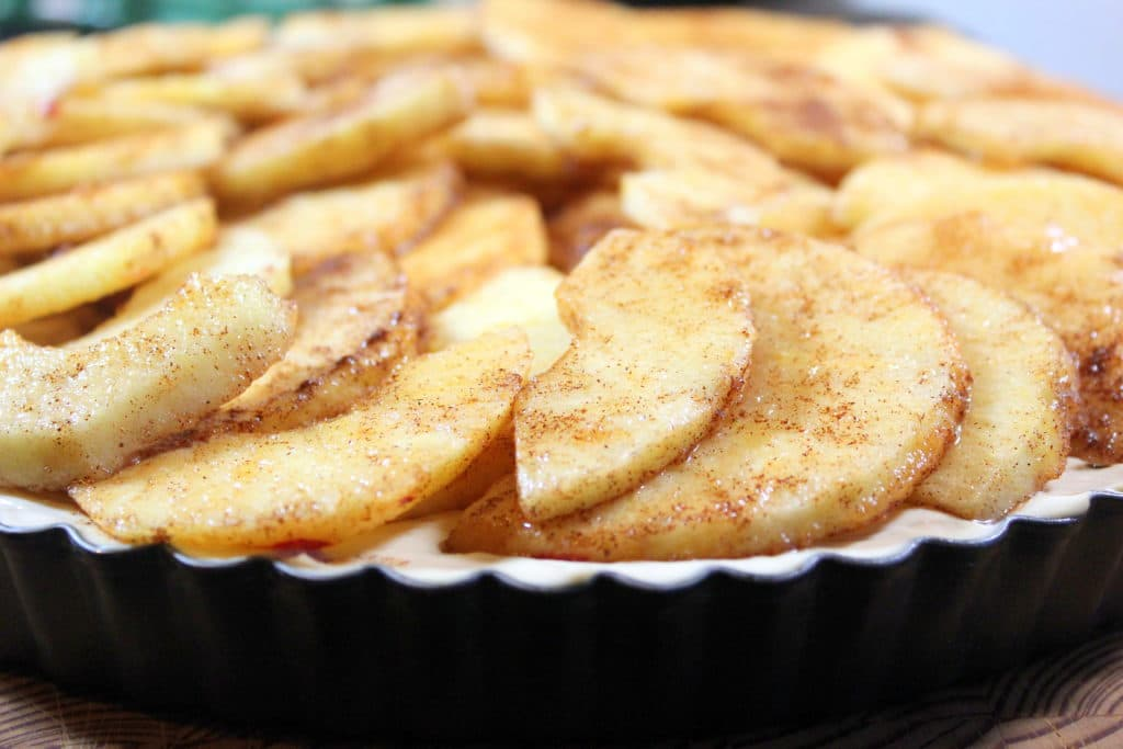 Close up of sliced apples in tart pan.